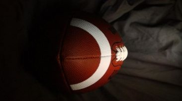 Photo of a football with a gray background.